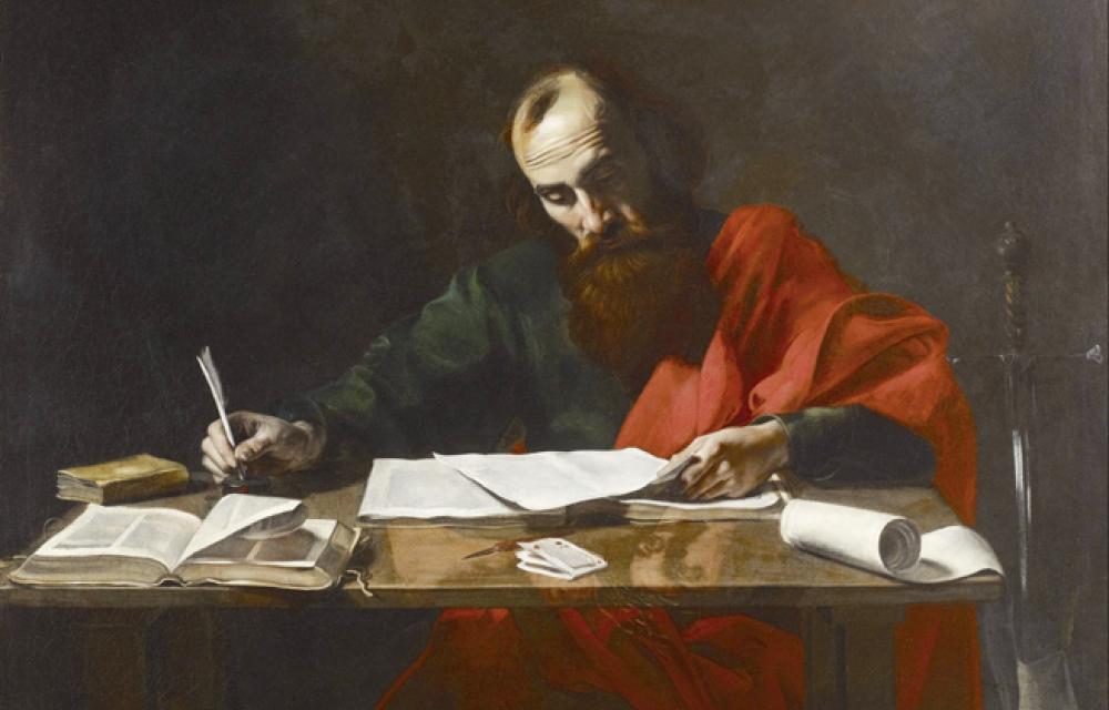 En man med skägg sitter vid ett skrivbord, iklädd med en svart tunica med röd toga. Han doppar gåspennan i bläckhorn och håller ett papper med den andra handen. Bordet är täckt med papperna.